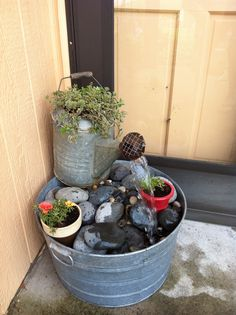 Water fountain I made from an old watering can  and wash tub, I used a small submersible pump from a broken fountain ( which I made into a birdbath, Mexican blue river rocks supported by hardware screen.  Sounds so nice on my porch.