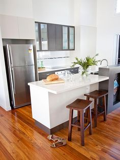 This modern kitchen incorporates warm hardwood floors with an all-white kitchen island and custom built-in cabinets to create a light and airy space.