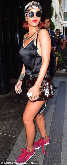 Casual chic: Rihanna made a fashionble arrival at her hotel as she donned a black silk frock reminiscent of a nightgown featuring a thigh-high spllit