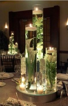 The table centerpieces will be tall vases at varying heights filled with submerged white calla lilies, white roses and white tulips with floating candles on top. Gorgeous for wedding centerpiece Decoration Table, Table Centerpieces, Wedding Centerpieces, Wedding Decorations, Centerpiece Ideas, Submerged Centerpiece, Quinceanera Centerpieces, Centerpiece Flowers, Elegant Centerpieces