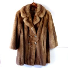 Vintage brown stroller length, genuine mink coat from the 1960s, size medium.  The fur on this coat is a beautiful autumn haze shade. It is a double breasted style with raglan sleeves and the fur is very soft, and fluffy. The sleeves have a deep hem which enables them to be cuffed if you wish. It is lined in beautiful satin and has a lovely monogram. There are two outside pockets and one hidden interior pocket and there is a button at the collar. It doesnt have a label.  It is very good…