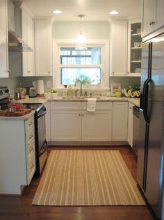 Nice color palette for a small kitchen: cream-colored granite, white cabinets, and light blue walls with stainless steel appliances and a deep wood floor