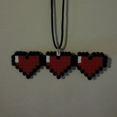 Retro styled Zelda Necklace in the shape of the power meter from the Zelda series of games. Made from black, white and red hama beads this Zelda Necklace is a great gift for any fan. Complete with a 30″ cord necklace that can be shortened or detached this Zelda Necklace is a great gift for birthdays, Christmases or any big occasion