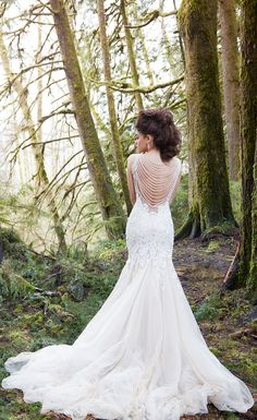 A chic vintage-inspired wedding dress with a fit and flare silhouette and a draped beaded back.