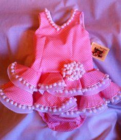 Traje flamenca niña ,popelín  con fondo rosa y lunar blanco, madroño en orilla y escote