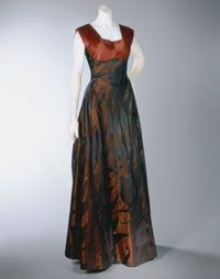 Elsa Schiaparelli evening dress and jacket spring 1948. Magnificent fabrics color bronze and black striped jacket cut away at the front, bells out over the hips, then curves and turns in at the back. The striped fabric is used again on the bodice to emphasize the contours of the bosom. The dress dramatic full skirt, although flat at the front, ties up into a slight bustle at the back. Made from bronze and black rayon damask and silk satin woven with a sweeping design of elongated tulips…