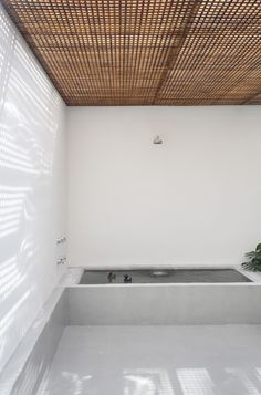 Stylish minimalist bathroom design with wooden ceiling and walls in white color