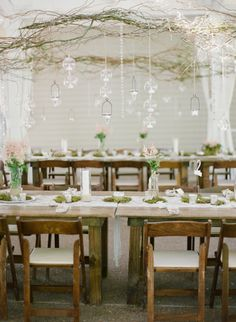 Jacque + Jon had a custom floor plan featuring this rustic farm tables and custom built chandeliers. The result was completely unique and stunning!  Nashville Garden Wedding and Reception Venue: CJ's Off the Square  Nashville Garden Wedding Anthropologie Style