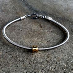 Bass String Bracelet, made from recycled bass strings, is a must-have accessory for any concert. Show your love (and support) for music—a portion of the proceeds from each purchase is donated to the Carter Albrecht Music Foundation. Diy Bracelets How To Make, Handmade Bracelets, Bracelets For Men, Handmade Jewelry, Bracelet Men, Bangle Bracelets, Guitar String Bracelet, String Bracelets, Bracelet Making