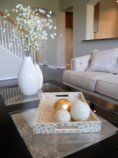 Coffee table staging ideas.  Simple tray with miss matched spheres, two vases & floral sprigs from Pier1.