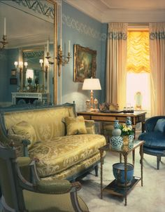 Embroidery and eglomise grace the walls, curtains and mirrors of this charming sitting room.