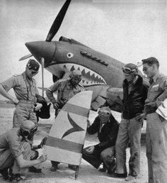 Pilots Check Out Rudder Shot Off Jap Plane - Jap rudder from plane shot down near the field is exhibited by (from left), Pilots Hill, Bacon, Cole, Rector, Lawlor, Schiel. In the background is shark-faced P-40. These men, plus those in jeep car at right, plus two below, make up most of the pilots of this particular squadron of American Volunteer Group. This is an extremely handy group of men.