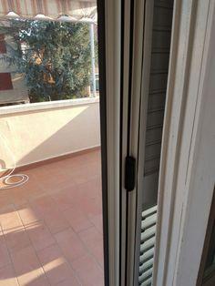zanzariere per porta finestra in bianco goffrato con chiusura decentrata