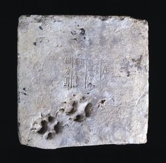 A brick from the ziggurat at Ur with a cuneiform inscription & accidentally impressed dog's paw-marks near one edge