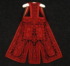 ALBANIAN EMBROIDERED VEST, EARLY 20th C. Long black wool felt densely embroidered with red cotton floral, having red felt trim, printed cotton twill lining. B-28, L-29. (Lining stained, wear inside neck and to felt at hem) exterior excellent.