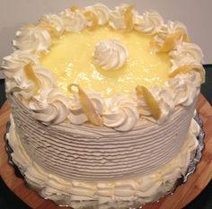 Lemon Parfait Cake Airy lemon mousse and vanilla sponge cake surrounded by whipped cream; topped with fresh fondant lemon wedges and a lemon spread glaze.