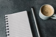 Blank empty notepad, pencil and cup of coffee on grey desk