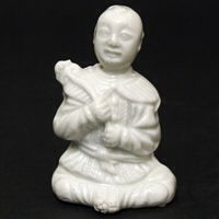 Blanc de Chine Porcelain. A Blanc de Chine Porcelain Water-Dropper Modelled as a seated Boy. Kangxi Period, Dehua Kilns Fujian Province. For a very similar figure see : Blanc de Chine, Porcelain From Dehua. A Catalogue of the Hickley Collection (Rose Kerr & John Ayres, Art Media Resources Ltd 2002) plate 45. Provenance : R & G McPherson Antiques (Stock number 15627) The Margaret Goldney Collection of Chinese Ceramics and Works of Art. R and G McPherson dealers in antique Chinese porcelain