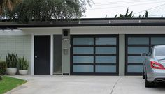 Eichler black front door, white pots, grey-green color and glass garage doors. Nice color palette.