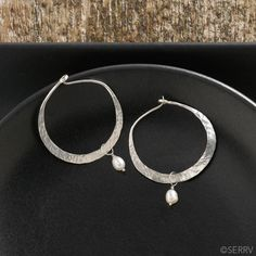 Silver Hoops with Pearl Earrings   Everyday sterling silver hoops are dressed up thanks to hand-hammered surfaces and white pearl drops. Wire loop closures.