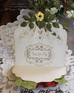 Paper: Carnation White, Cerise, Moss, Daffodil Stamps: Heart to Heart (Stamp Simply Ribbon Store) Dies: Labels 18, Nested Leaves, Rose Creations, Grand Labels Four, Foliage, Blossom Three Ink: Vintage Photo, Old Olive, Scattered Straw, Encore Gold Metallic Ink Accessories: EH1867, Anja's Style 2 – Flower, Brass Stencil, 18 Kt. Krylon Gold Leafing Pen, Grand Calibur, Zip Dry Adhesive, Perga Glue, Craft Knife, Flower Soft, Sponges, Embossing Tools, Embossing Mat