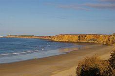 """Playa Fuente del Gallo. Conil de la Frontera  En bajamar se puede apreciar un conjunto rocoso aislado en el mar conocido popularmente como """"Las Tres Piedras"""""""