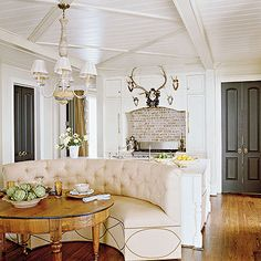 LOVE the couch, table, floors, ceiling, island, countertops, doors, light brick and antlers!