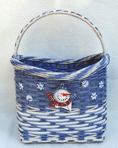 """WINTER WONDERLAND- It begins with a woven base and D handle in center.  Learn to arrow twine, continuous twine using blue round reed and ¼"""" flat oval, descending weaving, a decorative wrapped handle with a 2-tone braided rim.  This adorable basket can be whitewashed (directions included in pattern) and decorated for winter with a hand painted leather star snowman and 6 snowflakes all included in kit."""