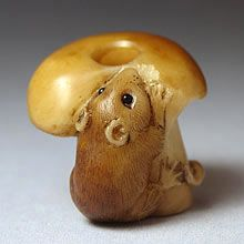 Mouse on a mushroom - Carved from tagua nut and stained. The eyes are inlaid from jet. This is a contemporary version of an ojime carved by Sergei Osipov. - Ojime (lit. cord fastener) is a type of bead which originated in Japan. They were worn between the inro and netsuke and typically under an inch in length. (Wikipedia)