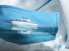 The timeless men's polo shirt by Princess Yachts in partnership with Thomas Pink featuring an illustration of Project 31, the first model produced by Princess 50 years ago, under-collar.