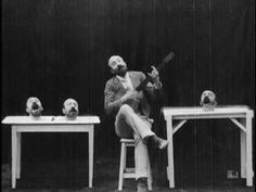 George Méliès accompanies three of his heads on the banjo