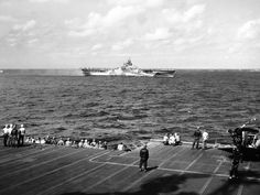 USS TICONDEROGA viewed from ESSEX CV-9 shortly after her fires have been extinguished. Note the wrecked plane aboard ESSEX at right.  -U.S. Navy photo in NARA record group 80-G-273056