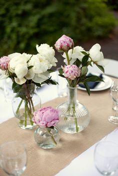 """Esprit """"vintage"""" pour ce centre de table réalisé à partir de belles pivoines simplement glissées dans de vieux flacons. centre de table #mariage #fleurs"""