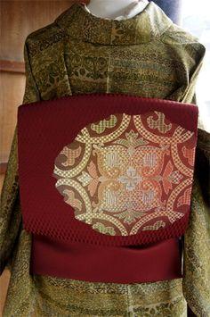 変わり市松のパターンが浮かぶ、こっくりと深いボルドーレッドに近いブラウンに、コーラルピンクやミントグリーンなどの綺麗色が優しくとけあうようにぼかされた綺麗色で、ヨーロッパのビンテージレースを思わせるような装飾模様が織り出された開き名古屋帯です。