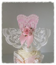 Birthday decoration This elegant dress was handmade from a soft white lace. The bodice is backed by pink scrapbook paper to give it extra strength and a pop of pink. The waist is accented with a mulberry rose and satin ribbons. So pretty on a cupcake. You can get it with an extra long