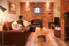 Living room at Shire Cottage, Holt, North Norfolk.  Reclaimed Victorian pine floor. Exposed brick and flint wall. Original inglenook fireplace. Sloane leather corner sofa in Old English Hazel by Darlings of Chelsea.