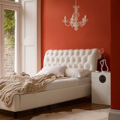 Orange Bedroom With White Accessories ~ Make a feature of your bed by painting the wall behind it a bright color. Team with white accessories for a striking finish.