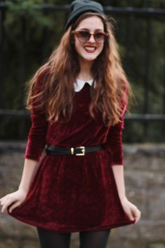 Red velvet dress cinched at the waist with a black belt.