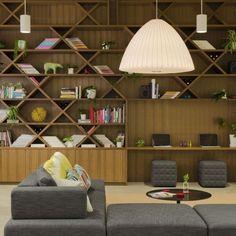 bibliothèque murale design en bois dans le salon avec canapé gris, suspensions élégantes et coin bureau