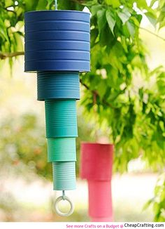 Thread a string with a wood ring through overlapping tin cans of increasing size and color intensity for an affordable backyard upgrade. Get the tutorial at Cheap Crafting.   - CountryLiving.com