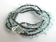 $24.99 The clear blue beads in this bracelet are tumbled/polished chips of aqua glass and crocheted onto a polyester faux sinew cord with a silver-plated toggle clasp.