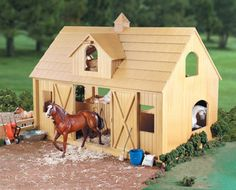 """The deluxe barn fits up to two Traditional Series horses. Includes two stalls with mats and built-in feed bins, sliding doors, hay loft, saddle and bridle rack and cross tie area. Made of natural wood. Assembled barn measures 30.5""""L x 21""""H x 18.5""""D. (Assembly required)."""