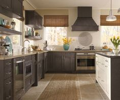 Shaker style cabinets have a lovely adaptability, making them useful for traditional or transitional styles. In this kitchen, symmetrically matched pairs of cabinets, open selves and windows create a setting of simple lines in which the dramatic wood hood has the presence of a great piece of art.