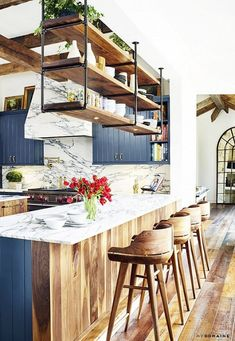Kitchen with a bar, dark blue cabinents and marble