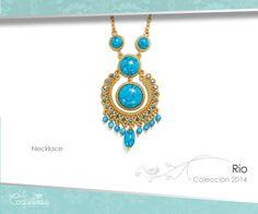 Collar dorado con piedras color turquesa. El pendiente es acentuado con Cristales Austríacos color azul claro y las gotas de perlas de color turquesa.