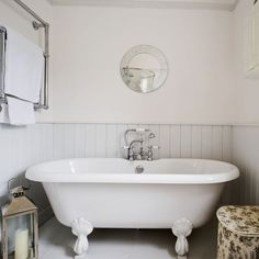 Calming country bathroom. Tongue-and-groove panelling injects instant country-cottage style into this bathroom. A double-ended freestanding bath with the mixer in the middle makes it ideal for two to share, and a large lantern adds romantic lighting. A towel rack is mounted high on the wall to save space, and floral storage boxes tuck away toiletries. #bathroom #toilet #shower