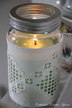 Hardanger Embroidery; a vintage piece of hardanger was adapted to make this mason jar candle cover; lace was added to the edges and ties were made for the back