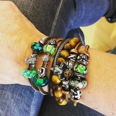 Trollbeads leather bracelet in brown with silver and glass beads in green paired with copper bangles
