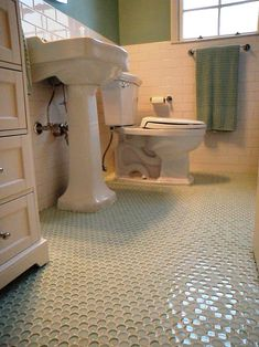 1940s bathroom update with glass penny round floor and white subway wall tile.