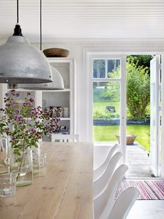 Anna and Michael Truelsen's serene kitchen overlooking the garden of their Swedish farmhouse. The slightly industrial light fittings work beautifully with the wood and moulded white chairs